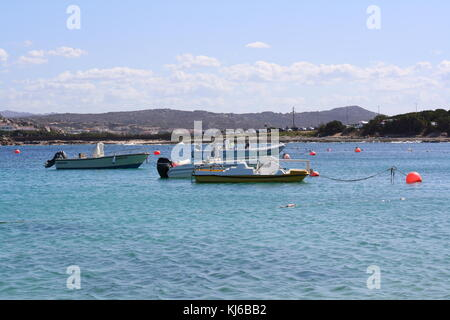 Small fishing boats anchoring in a bay with Sardinian water. - Stock Photo