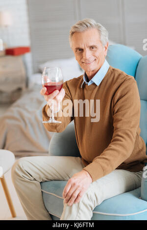 Smiling elderly gentleman drinking red wine at home - Stock Photo