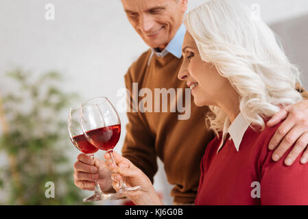 Cheerful married couple drinking red wine - Stock Photo