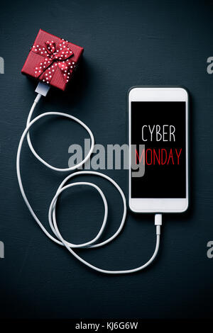 high-angle shot of a smartphone with the text happy cyber monday in its screen, connected to a gift by a cable, - Stock Photo
