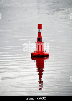 A red channel marker buoy in the Port of Tees with solar powered lighting. Ships must leave this buoy to their port - Stock Photo