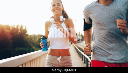 Attractive man and beautiful woman jogging together - Stock Photo