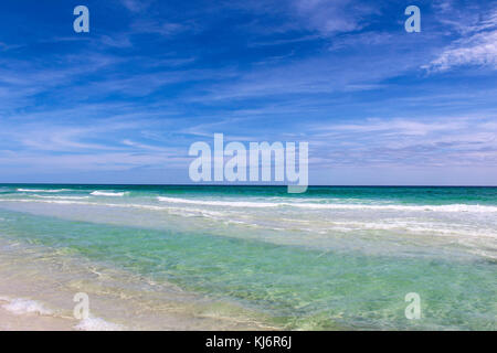tranquil landscape of the waves calmly crashing on to the sand on a hot summer day - Stock Photo