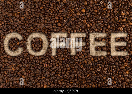 Coffee text on roasted beans and jute bag or sack as written letters concept - Stock Photo