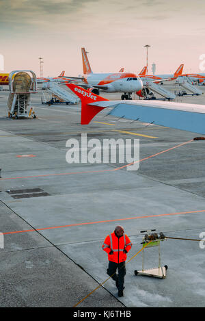 Milan Malpensa, Italy - November 21st, 2017:  Airport perssonel and rows of Easyjet Airbus A320 airplanes at Milan - Stock Photo