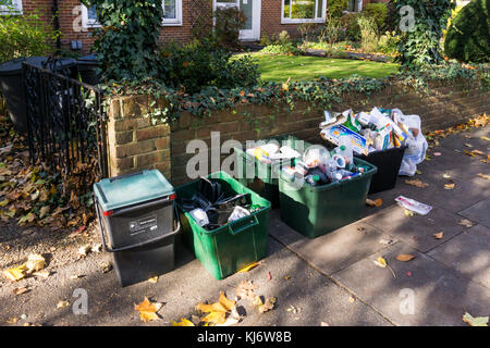 Household food waste, plastic, glass, metal and paper recycling put out in separate boxes on the pavement for collection - Stock Photo