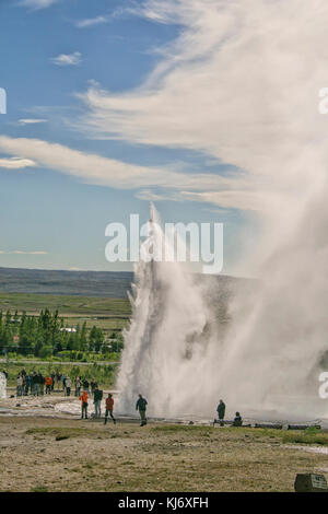 People watching the Strokkur geyser in Iceland erupting - Stock Photo