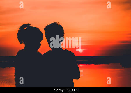 Young couple in love, silhouettes. Little boy and girl are having fun, in the background there is a beautiful sunset - Stock Photo