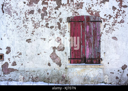 An old window with closed red worn wooden shutters on a white decrepit wall in winter with copy space. - Stock Photo