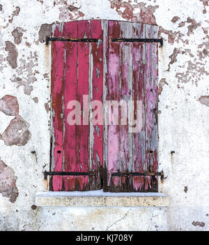 Close-up of an old window with closed red worn wooden shutters on a white decrepit wall in winter. - Stock Photo