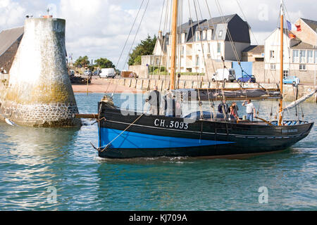 St Vaast harbour entrance showing Quai de Tourville and traditional fishing vessel 'Marie-Madeleine' leaving the - Stock Photo
