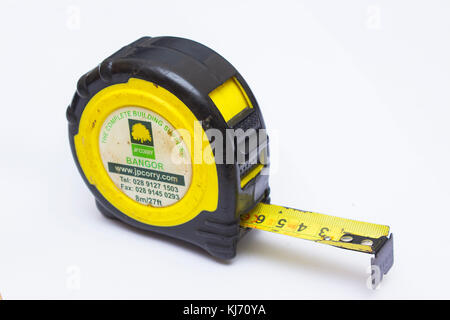 An old and well used retractable tape measure with metric and imperial measure bearing the suppliers name and address - Stock Photo