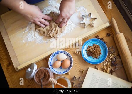Female hands kneading a ginger bread dough on a wooden board, ingredients , roller and cooking book in front of - Stock Photo