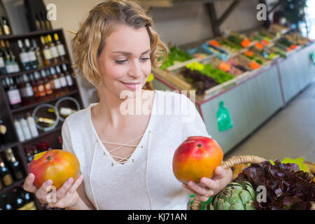 woman in greengrocers holding a mango in each hand - Stock Photo