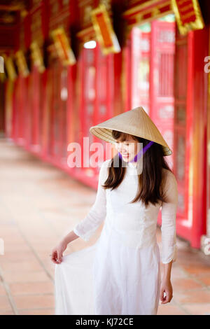 Young Vietnamese woman in a temple wearing a traditional Ao Dai dress and Non La Asian conical hat - Stock Photo