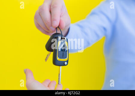 close up photo of male hand holding a car key. Person is wearing a blue shirt, standing in front of the bright yellow - Stock Photo