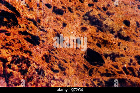 Obsidian mineral stone texture pattern macro view. Beautiful volcanic glass dark-red brown with black spots background - Stock Photo