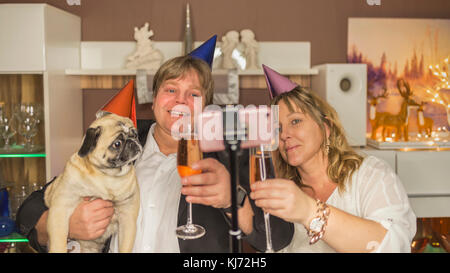 Middle aged couple makes with their pug a selfie during a New Year's Eve party at home - Stock Photo