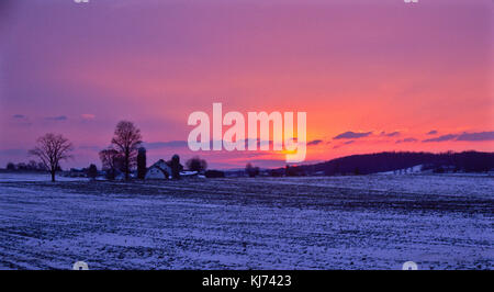 Colorful sunrise over the snow covered Amish farmland, Lancaster County, Prural Pennsylvania, USA, inspirational - Stock Photo