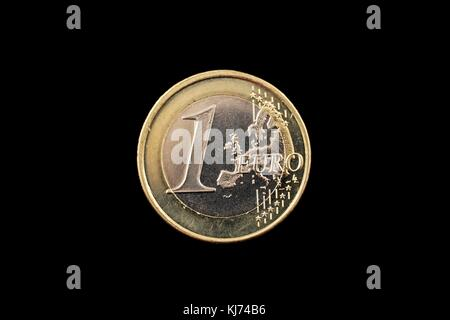 A macro image of a one euro coin isolated on a black background - Stock Photo