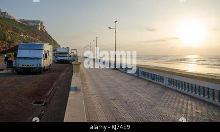Sidi Ifni, Morocco - September 20 2013: Motorhomes at campsite next to stone beach promenade during scenic sunset - Stock Photo