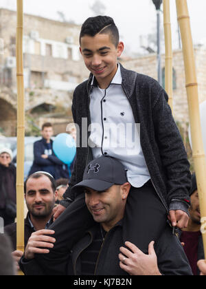 Teenage boy on shoulders of his father at Bar Mitzvah Celebration, Safed, Northern District, Israel - Stock Photo