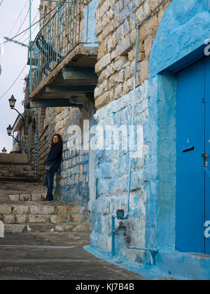 Woman leaning on stone wall in street, Safed, Northern District, Israel - Stock Photo