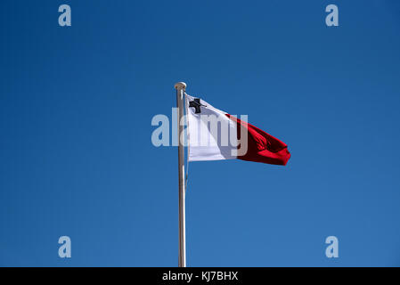 Maltese Flag against a blue sky fluttering in the wind - Stock Photo