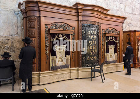 Jewish Men Praying Near Wooden Cabinet With Torah Scrolls In Cave Synagogue  Adjoining Western Wall,