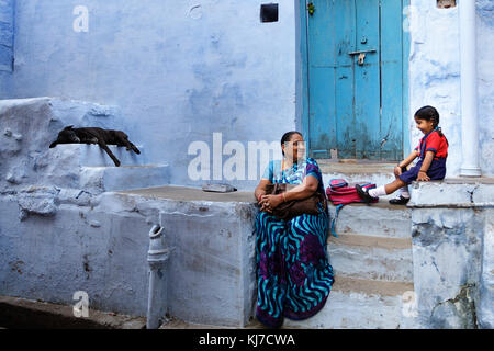 Happy little indian girl sitting on the stairs with her grandma in front of a blue house in Jodhpur, Rajasthan, - Stock Photo