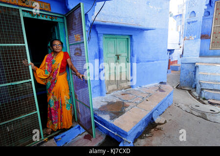 Old indian woman dressed in traditional clothes opening the green entrance door, Jodhpur, India. - Stock Photo