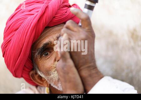 Member of ethnic minority - Rabari man smoking clay pipe. Photo taken at countryside near Jodhpur, Rajasthan, India. Stock Photo