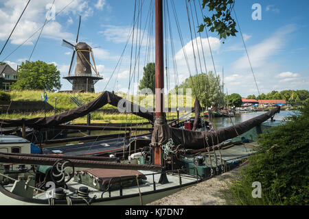 Typical Dutch Windmill Nooit Volmaakt in Gorinchem, Holland, with with historic sailing ships in the foreground - Stock Photo