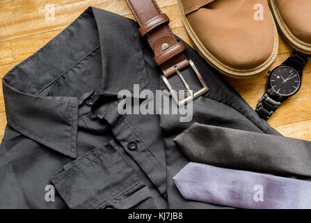 Men's clothes on top of a wooden surface, showing a black dress shirt, brown leather belt, brown boots, neckties - Stock Photo