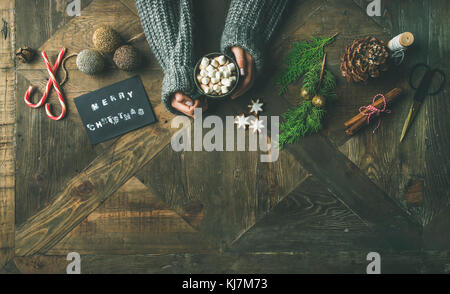 Christmas, New Year holiday preparation background. Flat-lay of greeting card, glittering toys, woman's hands holding - Stock Photo