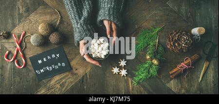 Christmas, New Year preparation background. Flat-lay of greeting card, glittering toy, woman's hands in grey sweater - Stock Photo