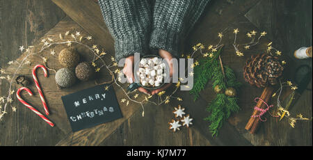 Christmas, New Year holiday background. Flat-lay of greeting card, glittering toys, woman's hands holding mug of - Stock Photo