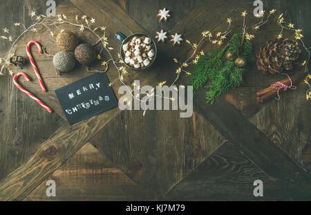 Christmas, New Year holiday background. Flat-lay of greeting card, glittering toys, mug of hot chocolate, cinnamon, - Stock Photo