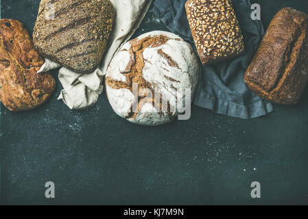 Various bread selection flat-lay. Top view of Rye, wheat and multigrain rustic bread loaves over black background, - Stock Photo