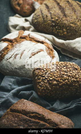 Various bread selection. Close-up of Rye, wheat and multigrain rustic bread loaves over black background - Stock Photo