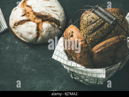 Various bread selection. Rye, wheat and multigrain rustic bread loaves on kitchen towels over black background, - Stock Photo