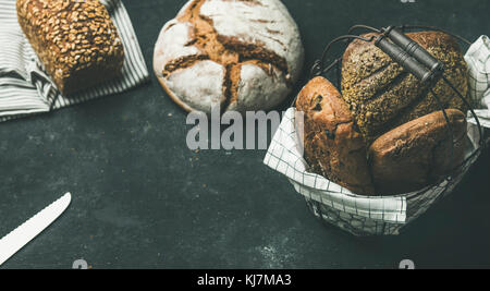 Various bread selection. Rye, wheat and multigrain rustic bread loaves over black background, copy space, horizontal - Stock Photo