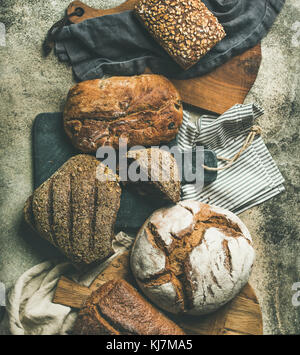 Flat-lay of various bread selection. Rye, wheat and multigrain rustic bread loaves on kitchen towels and wooden - Stock Photo