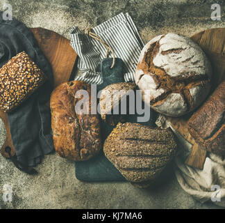 Flat-lay of various bread selection. Rye, wheat and multigrain rustic bread loaves on kitchen towels and boards - Stock Photo