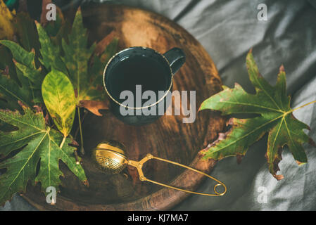 Fall morning tea in bed. Black mug of tea with sieve and colorful fallen leaves on rustic wooden tray over bed linen and blanket background, selective