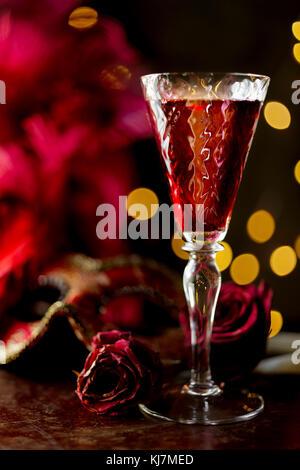 Red wine glass alongside chirstmas lights - Stock Photo