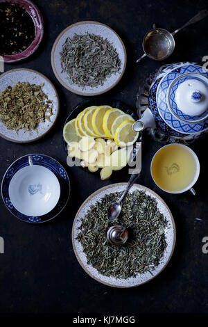 Different Tea Leaves with slices of lemon on a dark background - Stock Photo