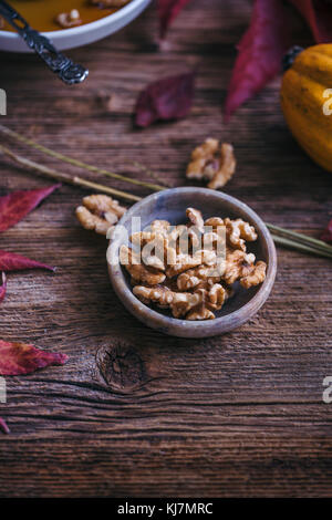 Walnuts in a little bowl on a rustic wooden table - Stock Photo