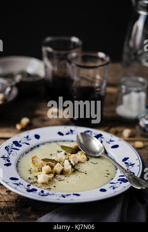 Cauliflower cream soup on a wooden dining table. Close-up - Stock Photo