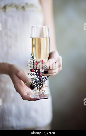 Celebrating with champagne. Young woman holding in her hands a glass of champagne - Stock Photo